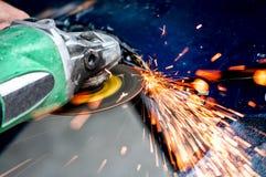 Schwerindustriearbeitskraft-Ausschnittstahl mit Winkelschleifer Stockfoto