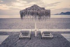 Schwermütige Strand- und Seeansicht mit Sonnenschutz an Sonnenuntergang chillout Farbe spaltete das Tonen auf stockfotografie