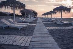 Schwermütige Strand- und Seeansicht mit Sonnenschutz an Sonnenuntergang chillout Farbe spaltete das Tonen auf lizenzfreie stockfotos
