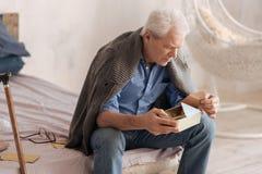 Schwermütiger älterer Mann, der einen Brief aus dem Kasten heraus nimmt Lizenzfreie Stockfotos