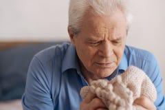 Schwermütiger älterer Mann, der seine wifes Jacke betrachtet Lizenzfreies Stockbild