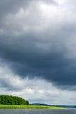 Schwermütiger Himmel über See. stockbilder