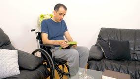 Schwermütiger trauriger junger behinderter Mann, der ein Foto betrachtet stock video