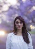 Schwermütiges Bild der Schönheit im weißen Kleid, das in der Straße umgeben durch purpurrote Jacarandabäume steht Lizenzfreie Stockfotos