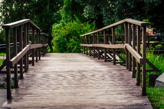 Schwermütiges Foto der Wodden-Brücke in einem Park, zwischen dem Holz - Desaturated, Weinlese-Blick stockbild
