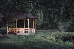 Schwermütiges Foto des hölzernen Sommer-Garten-Hauses in einem Park, zwischen stockfotos