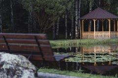 Schwermütiges Foto des hölzernen Sommer-Garten-Hauses in einem Park, zwischen stockbilder