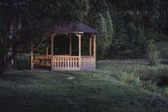 Schwermütiges Foto des hölzernen Sommer-Garten-Hauses in einem Park, zwischen lizenzfreie stockfotos