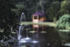 Schwermütiges Foto des hölzernen Sommer-Garten-Hauses in einem Park, zwischen lizenzfreies stockbild