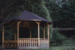 Schwermütiges Foto des hölzernen Sommer-Garten-Hauses in einem Park, zwischen lizenzfreie stockbilder
