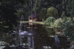 Schwermütiges Foto des hölzernen Sommer-Garten-Hauses in einem Park, zwischen stockbild