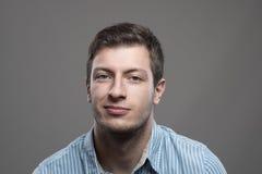 Schwermütiges Headshotporträt des jungen Mannes im blauen Hemd mit Grinsenlächeln Stockfotografie