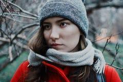 Schwermütiges Porträt der jungen erwachsenen Frau in den Niederlassungen von Bäumen während der blauen Stunde stockbild