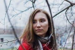 Schwermütiges Porträt der jungen erwachsenen Frau in den Niederlassungen von Bäumen während der blauen Stunde lizenzfreies stockbild