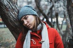 Schwermütiges Porträt der jungen erwachsenen Frau in den Niederlassungen von Bäumen während der blauen Stunde lizenzfreie stockfotos
