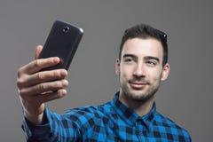 Schwermütiges Porträt des jungen überzeugten glücklichen Mannes, der Selbstporträt mit Handy nimmt Lizenzfreie Stockbilder