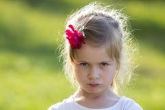 Schwermütiges recht kleines blondes Mädchen mit netten grauen Augen und Rotrose I Lizenzfreies Stockbild