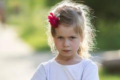 Schwermütiges recht kleines blondes Mädchen mit netten grauen Augen und Rotrose I Stockbilder