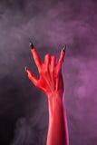 Schwermetallgeste, Hand des roten Teufels mit schwarzen Nägeln Stockbild