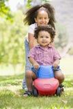 Schwester, die Bruder auf Spielzeug mit dem Radlächeln drückt Lizenzfreies Stockfoto