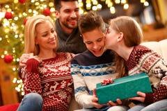 Schwester, die ihrem Bruder ein Weihnachtsgeschenk gibt und an ihn küsst stockfotos