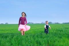 Schwester, die mit ihrem brather auf dem Gras runing ist Stockfoto