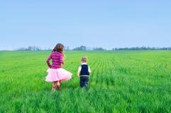 Schwester, die mit ihrem brather auf dem Gras runing ist Stockfotografie