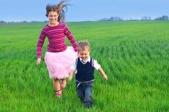 Schwester, die mit ihrem brather auf dem Gras runing ist Lizenzfreies Stockfoto