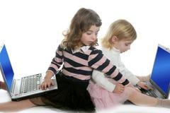 Schwester mit zwei kleinen Mädchen mit Computerlaptopen stockbilder