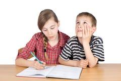 Schwester Teaching Maths zu ihrem jüngeren selbstlosen Bruder Isolated auf Weiß Stockfotografie