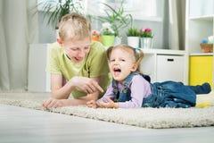 Schwester und Bruder, die in einem Raum spielen stockbild