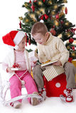 Schwester und Bruder, die Weihnachtsgeschenke zeigen Stockfotografie