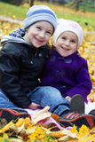 Schwester und Bruder zusammen auf Herbstlaub Stockfotografie