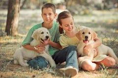 Schwesterbruder des jungen jugendlich der Szene des Retrieverwelpen genießen reizender, Sommerzeitferien mit Elfenbein weißes Lab lizenzfreies stockfoto