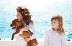 Schwesterkindmädchen mit Hund auf dem Meer Stockbild