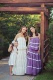 Schwestermädchen der blauen Augen der Kastanie des erstaunlichen Brunette entspringen die blonden, die das stilvolle weiße purpur Lizenzfreies Stockfoto