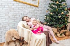 Schwestern auf Weihnachtsabend an verziertem Wohnzimmer Stockfotografie