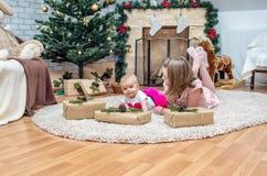 Schwestern auf Weihnachtsabend an verziertem Wohnzimmer mit Tradition Stockfotos