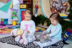 Schwestern in den Pyjamas, die im Raum spielen Das Konzept von Weihnachten Lizenzfreie Stockfotos