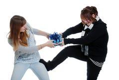 Schwestern, die über einem Geschenk kämpfen Lizenzfreie Stockfotografie
