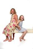 Schwestern, die auf Bank sitzen Lizenzfreie Stockfotografie