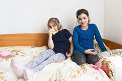 Schwestern, die auf der Couch sitzen lizenzfreie stockbilder
