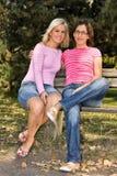 Schwestern, die auf einer Bank sitzen Lizenzfreie Stockfotografie