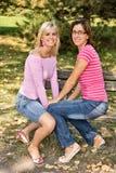 Schwestern, die auf einer Bank sitzen Stockbild