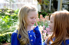 Schwestern, die in den Gärten spielen Stockfotos