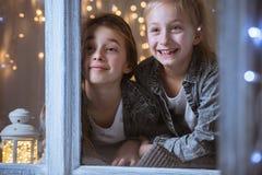 Schwestern, die durch das Fenster schauen stockbild