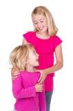Schwestern, die einander umarmen und betrachten Stockbild
