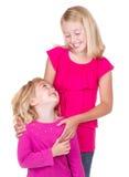 Schwestern, die einander umarmen und betrachten Lizenzfreies Stockbild
