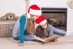 Schwestern, die eine Weihnachtsgeschichte lesen Stockfotografie