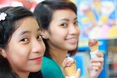 Schwestern, die Eiscreme genießen Stockfotografie